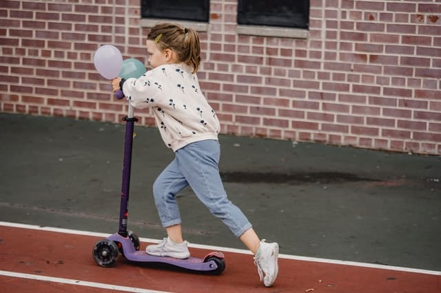 a small girl on a scooter